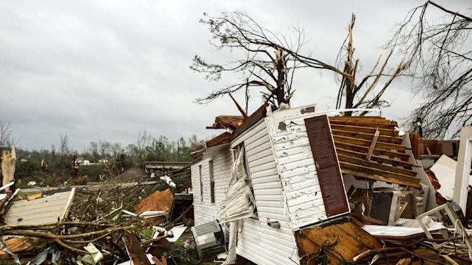 Hunter Allred attempts to coax out a cat that was underneath a home along Clayton Ave in Tupelo, Miss., Monday, April 28, 2014. Allred was helping the home's owner who had returned looking for pets after a severe weather system blew through the South. (AP Photo/The Commercial Appeal, Brad Vest)