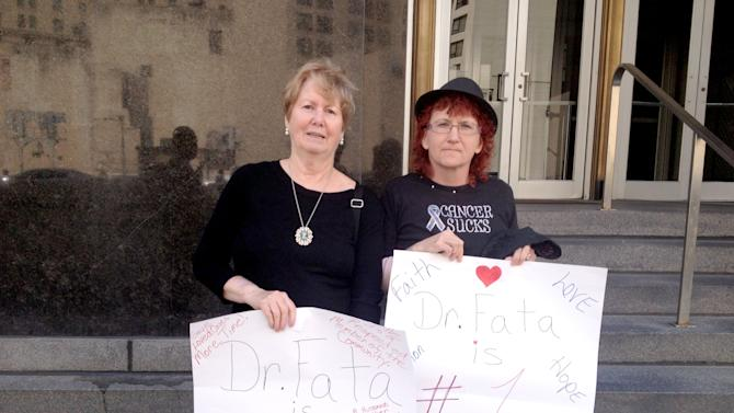 Sally Kelly, 70, left, of Lake Orion, Mich. and Theresa Pickering, 48, of Dryden, Mich., both cancer patients of Dr. Farid Fata, hold signs outside Federal Court in Detroit on Tuesday, Aug. 13, 2013 in support of the Oakland Township oncologist. Last week, federal prosecutors charged Fata with fraud, accusing him of deliberately misdiagnosing patients and ordering chemotherapy for others who were in remission or had no chance of surviving, all to reap millions from the Medicare program. (AP Photo/Detroit Free Press, Tresa Baldas) DETROIT NEWS OUT, TV OUT, INTERNET OUT, MAGS OUT, NO SALES, MANDATORY CREDIT DETROIT FREE PRESS