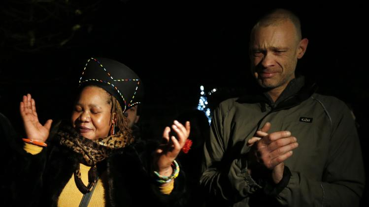 Two people sing at a gathering in memory of Nelson Mandela outside the South African High Commission across from Trafalgar Square in London