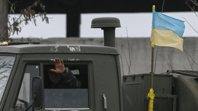 Member of the Ukrainian armed forces waves on a military vehicle near Artemivsk