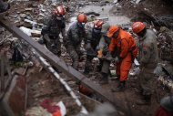 Rescue workers try to recover the body of a landslide victim in Nova Friburgo, Brazil, Saturday, Jan. 15, 2011. After four nights of torrential rains, mudslides have killed more than 500 people in the Rio de Janeiro area.