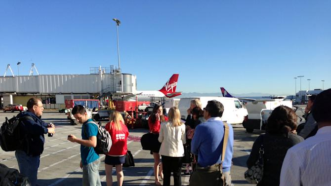 In this photo provided by John Forstrom, which has been authenticated based on its contents and other AP reporting, people wait on the tarmac at Los Angeles International Airport, Friday, Nov. 1, 2013. Shots were fired Friday at Los Angeles International Airport, prompting authorities to evacuate a terminal and stop flights headed for the city from taking off from other airports.(AP Photo/John Forstrom)