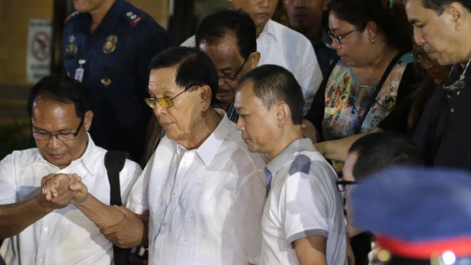 Former Senate President Juan Ponce Enrile, second left, is helped to a waiting ambulance after undergoing processing at the Philippine National Police upon his surrender on corruption charges Friday, July 4, 2014 at Camp Crame at suburban Quezon city, northeast of Manila, Philippines. Enrile, 90, surrendered Friday to face a charge of large-scale corruption, the most prominent of three top politicians to fall in a government anti-graft crackdown in recent weeks. (AP Photo/Bullit Marquez)