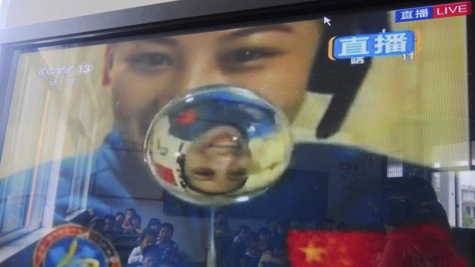 Elementary school students are reflected on the screen of a television showing a lecture delivered by Chinese female astronaut Wang Yaping onboard the Tiangong 1 prototype space station, in Taizhou in eastern China's Zhejiang province Thursday June 20, 2013. China held its first classroom lecture from its orbiting space station as part of efforts to popularize the successful manned space flight program among young people. (AP Photo) CHINA OUT