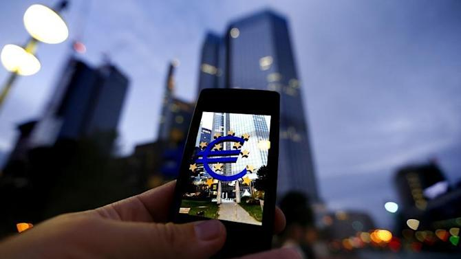 A passerby uses his smartphone to take a picture of the euro sign landmark in front of the headquarters of the European Central Bank (ECB) in Frankfurt
