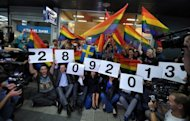 Gay activists sit at the entrance to a conference hall in central Belgrade on October 6. Serbia's gay activists vowed on Saturday to keep on with preparations for a pride parade next year despite a ban on this weekend's march for the second year in succession that has forced them to organise their gathering indoors