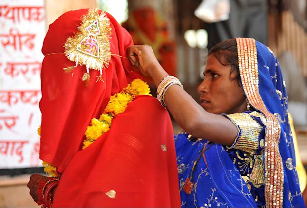 A woman adjusts the veil of her 15-year-old child bride daughter Sintu at the Balaji temple in Kamkheda village, in the western Indian state of Rajasthan, Saturday, May 7, 2011. Ignoring laws that ban