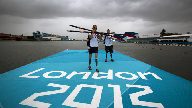 Rower Oksana Masters and her rowing partner Rob Jones from United States carry their oars after a training session ahead of the 2012 Paralympics Olympics in Eton Dorney, near Windsor, England, Wednesday, Aug. 29, 2012. The opening ceremony for the Paralympic Games will be held at London's Olympic Park on Wednesday Aug. 29. (AP Photo/Emilio Morenatti)