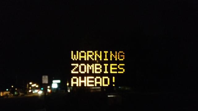 "In a photo provided by WGME/TV, a sign at a road construction site was changed by a hacker to read ""Warning Zombies Ahead!"" in Portland, Maine, Wednesday, Oct. 10, 2012. It originally read ""Night work 8 pm-6 am. Expect delays."" Drivers may have gotten a chuckle out of an electronic message board in Maine warning of zombies, but city officials were not amused. (AP Photo/Jeff Peterson, WGME/TV)"