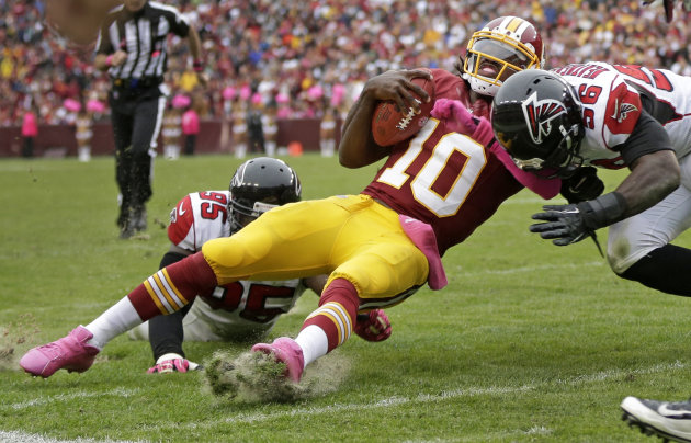 Washington Redskins quarterback Robert Griffin III is hit by Atlanta Falcons defensive end Jonathan Massaquoi (96) and defensive tackle Jonathan Babineaux (95) during the second half of an NFL footbal