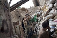 Rebel fighters shoot over a barricade towards regime positions in Aleppo on September 18, 2013