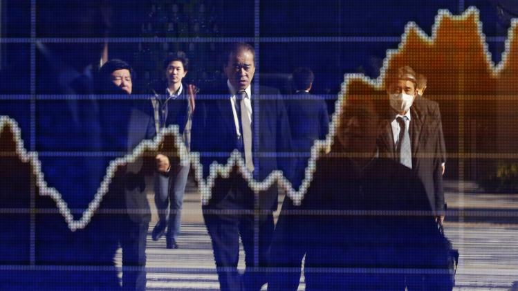 Pedestrians are reflected in an electronic board showing a graph of recent fluctuations of Japan's Nikkei average outside a brokerage in Tokyo