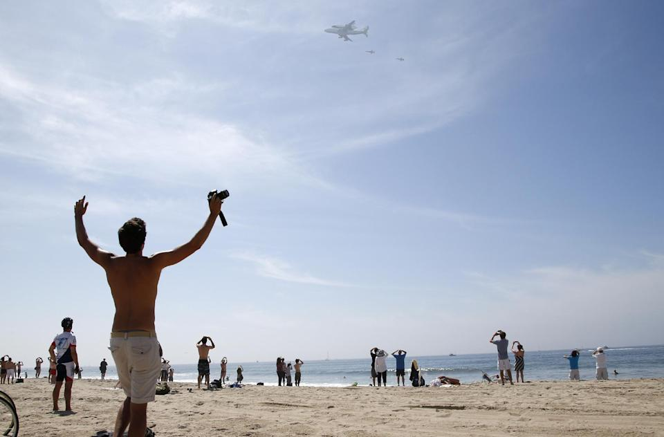 Spectators watch as the Space Shuttle Endeavour mounted on NASA's Shuttle Carrier Aircraft (SCA) flies near Santa Monica, Calif., Friday, Sept. 21, 2012. (AP Photo/Jae C. Hong)