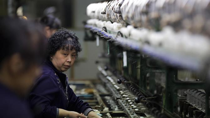In this April 16, 2015 photo, women work in front of reeling machines at a silk factory in Suzhou in east China's Jiangsu province. China's Central Bank said Sunday, April 19, 2015 that it will cut its bank reserve requirement ratio by 1 percentage point to stimulate more lending into a slowing economy. (AP Photo/Andy Wong)