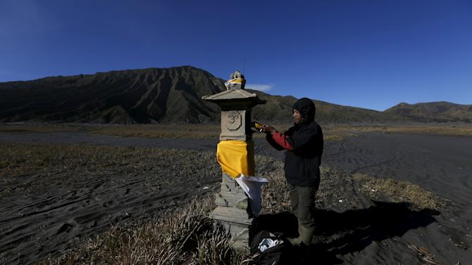 A Hindu villager puts an offering at an altar ahead of the annual Kasada festival at Mount Bromo