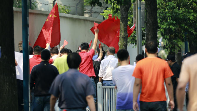 A small group of Chinese protesters march while shouting anti-Japan slogans in front of the Japanese Consulate General in Shanghai, China, Wednesday, Sept. 19, 2012. (AP Photo/Eugene Hoshiko)