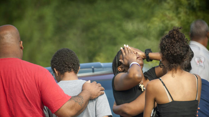 People comfort each other after a shooting in Fayetteville, N.C., Wednesday, July 30, 2014. A domestic dispute erupted into a gun battle with deputies Wednesday at a North Carolina mobile home park, leaving three people dead and three officers wounded, officials said. (AP Photo/The Fayetteville Observer, Cindy Burnham) MANDATORY CREDIT