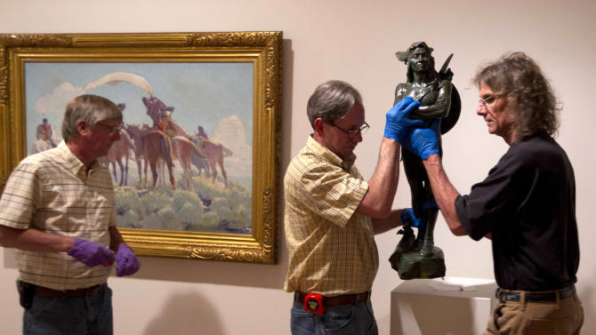"In a photo made Friday, June 28, 2013, Scott Mosher, left, Stew Henderson, center, and Michael Hudak install Hermon Atkin MacNeil's bronze statue titled ""A Chief of the Multnomah Tribe"" at the Colby College Museum of Art in Waterville, Maine. At left is William Herbert Dunton's oil painting, ""Buffalo Signal.""(AP Photo/Robert F. Bukaty)"