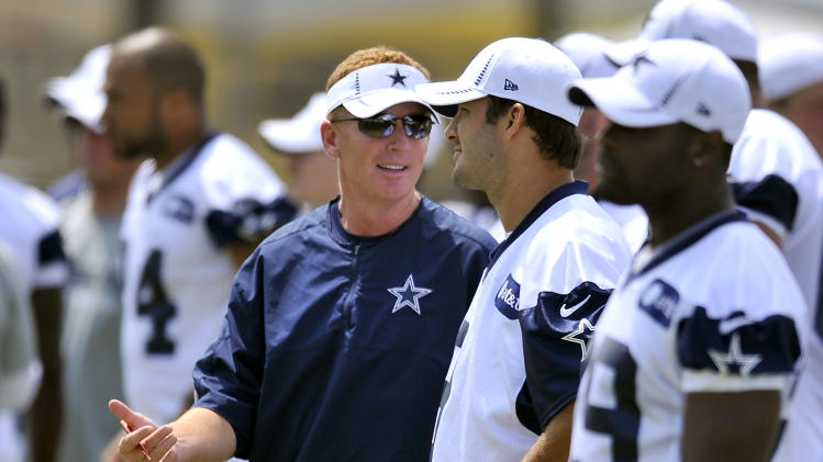 Dallas Cowboys head coach Jason Garrett, left, talks things over with quarterback Tony Romo, right, in between plays during NFL football training camp, Friday, Aug. 3, 2012, in Oxnard, Calif. (AP Photo/Gus Ruelas)