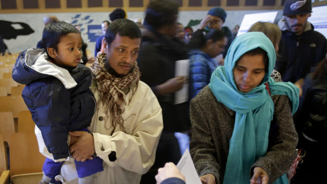 """Afroj Sultana, right, her husband Md Rahman and her son Mohammed Usman, 2, talk with volunteers about collecting relief funds at a school auditorium in the Rockaways section of New York, Thursday, Jan. 10, 2013. The New York City financial services firm that lost the most workers in the Sept. 11 terror attacks announced that it will """"adopt"""" 19 schools in communities hit hard by Superstorm Sandy and give a total of $10 million to families in those schools. (AP Photo/Seth Wenig)"""