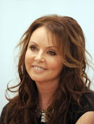 Famed British singer Sarah Brightman smiles during her press conference in Moscow. Brightman told AFP: &quot;I will be the first (musician in space) and would like to experiment and see how I can sing from space and I would like to connect with the Earth in some way.&quot;