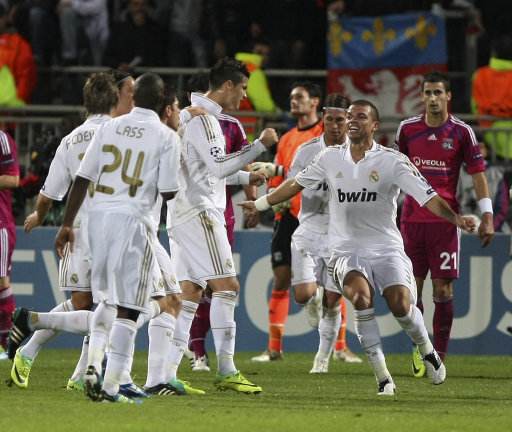 Real Madrid's players celebrate after Real Madrid's Portuguese forward Cristiano Ronaldo, center, scored against Lyon during their Group D Champions League soccer match, at Gerland Stadium, in Lyon, central France, Wednesday, Nov. 2, 2011. (AP Photo/Claude Paris)