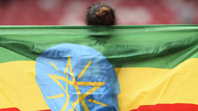 Dibaba holds her national flag after winning the women's marathon at the 15th IAAF Championships in Beijing