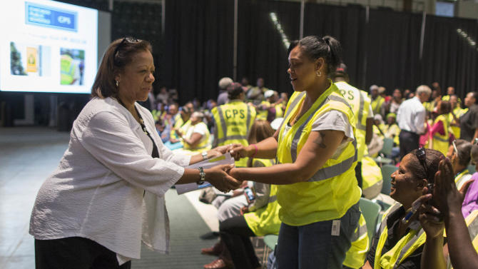 Chicago Public Schools CEO Barbara Byrd-Bennett holds hands with a member of the Safe Passage program after she spoke during a training session at Chicago State University in Chicago, Wednesday, Aug. 21, 2013. (AP Photo/Scott Eisen)