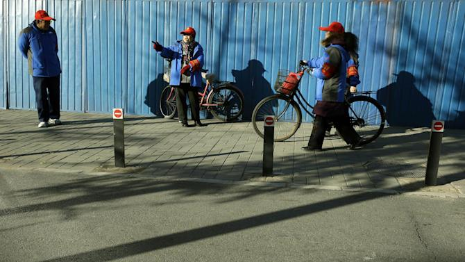 Public security volunteers patrol the streets during the 18th Communist Party Congress held in Beijing, China, Monday, Nov. 12, 2012. (AP Photo/Ng Han Guan)