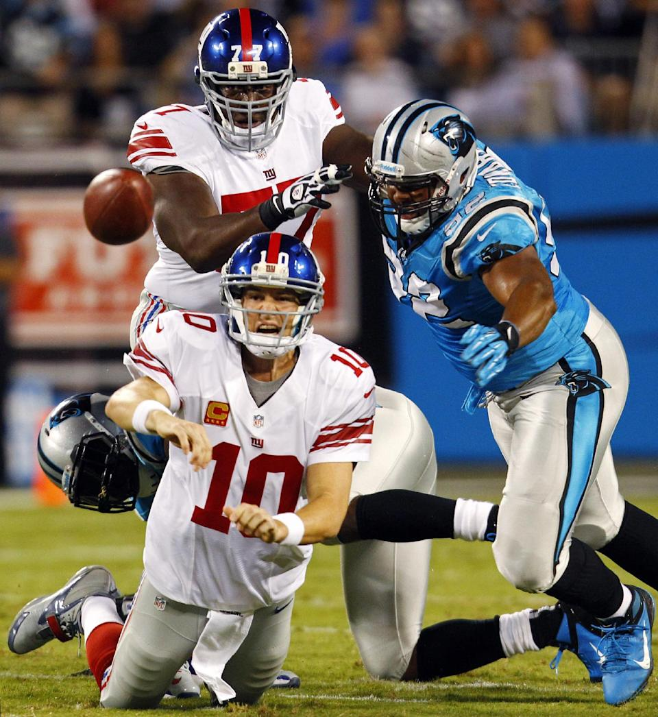 New York Giants quarterback Eli Manning (10) throws a pass under pressure from Carolina Panthers defensive tackle Dwan Edwards (92) during the first quarter of an NFL football game in Charlotte, N.C., Thursday, Sept. 20, 2012. (AP Photo/Chuck Burton)