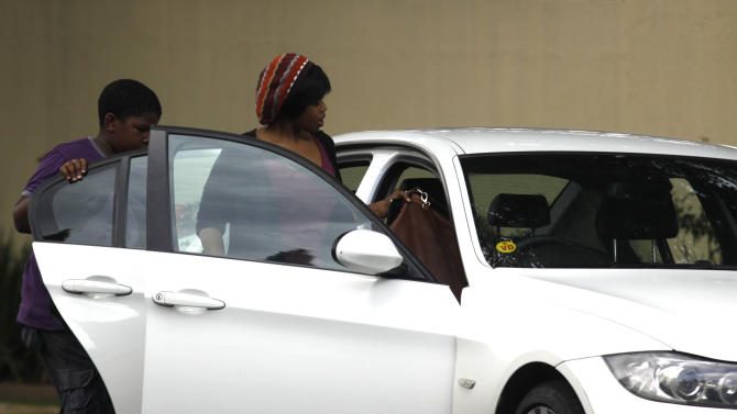 An unidentified woman and chilldren leave the Johannesburg home of former president Nelson Mandela after a visit Friday, Dec. 28, 2012. Mandela who was admitted to hospital Dec 8, with a lung infection and underwent gall stone surgery, is now receiving medical care at home after being discharged Wednesday. (AP Photo/Denis Farrell)
