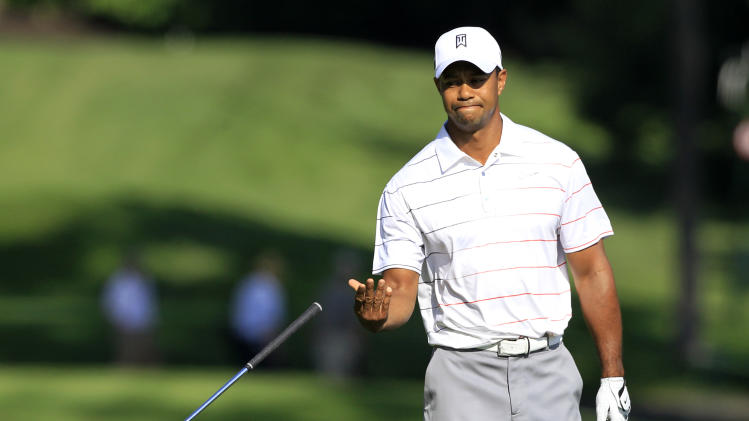 Tiger Woods throws his club after hitting to the 13th green from the fairway during the first round of the Memorial golf tournament at the Muirfield Village Golf Club in Dublin, Ohio, Thursday, May 31, 2012. (AP Photo/Tony Dejak)