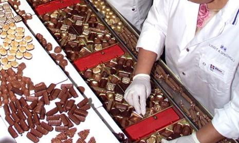 Employees in a Swiss chocolate factory: On average, every man, woman, and child in Switzerland eats 120 bars of chocolate each year.