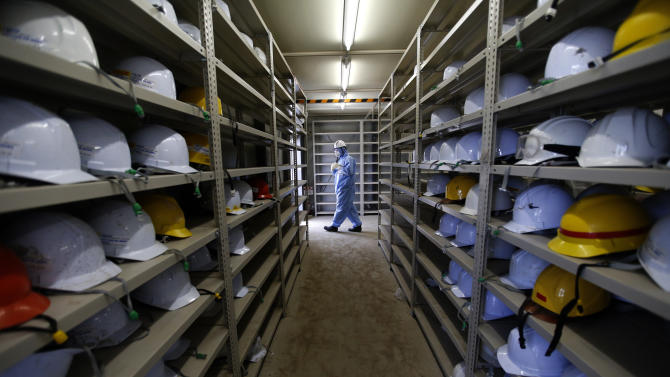 A worker, wearing a protective suit and a mask, leaves a room with shelves lined with helmets at Tokyo Electric Power Co's tsunami-crippled Fukushima Daiichi nuclear power plant in Okuma town