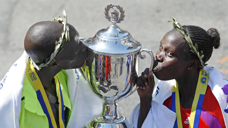 Wesley Korir, left, and Sharon Cherop, both of Kenya,  kiss the winner's trophy after winning the men's and women's divisions of the 116th Boston Marathon in Boston, Monday, April 16, 2012. (AP Photo/Charles Krupa)