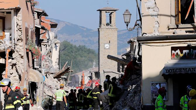 Firefighters and rescuers work following an earthquake in Amatrice