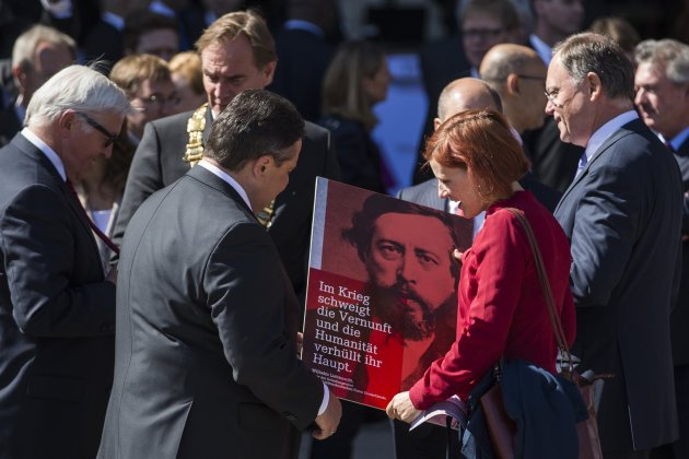 Kipping Die Linke Party presents placard with quote by Liebknecht to SPD leader Gabriel before ceremony marking 150th anniversary of foundation of Germany's social democratic party in Leipzig