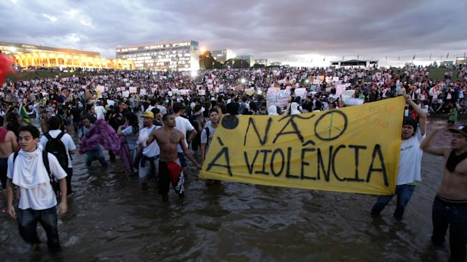 Demonstrators carry a sign reading in Portuguese 'No to violence' in Brasilia, Brazil, Monday, June 17, 2013. Protesters massed in at least seven Brazilian cities Monday for another round of demonstrations voicing disgruntlement about life in the country, raising questions about security during big events like the current Confederations Cup and a papal visit next month. (AP Photo/Eraldo Peres)