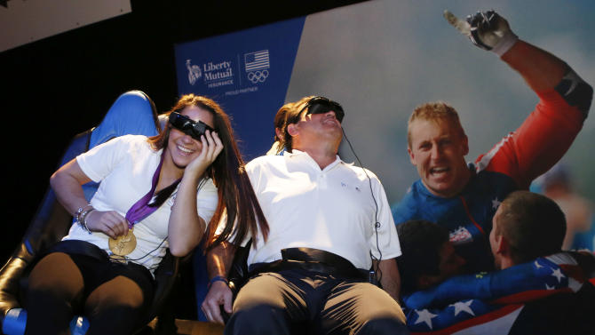 Two-time gold medal gymnast, Aly Raisman, left, and USA hockey team gold medalist, Mike Eruzione, right, alongside Olympians past and present, took part in festivities, celebrating One Year Out from the 2014 Olympic Winter Games on Thursday, Feb. 7, 2013 in Boston. (Photo by Bizuayehu Tesfaye/Invision for Liberty Mutual Insurance/AP Images)