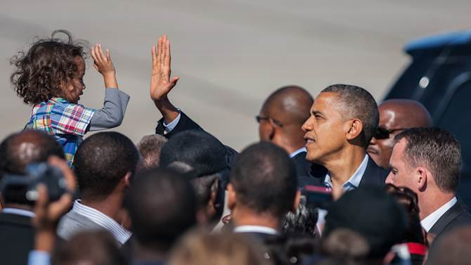 President Barack Obama high-fives with a child as he arrives at the Newport News/Williamsburg International Airport in Newport News, Va. on Saturday, Oct. 13, 2012. (AP Photo/Zach Gibson)