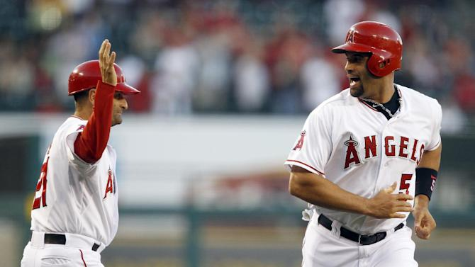 Los Angeles Angels' Albert Pujols, right, yells out to third base coach Dino Ebel, left, after rounding third to score on a two-run home run by Angels' Josh Hamilton  in the first inning against the Seattle Mariners during a baseball game Tuesday, May 21, 2013 in Anaheim.    (AP Photo/Alex Gallardo)
