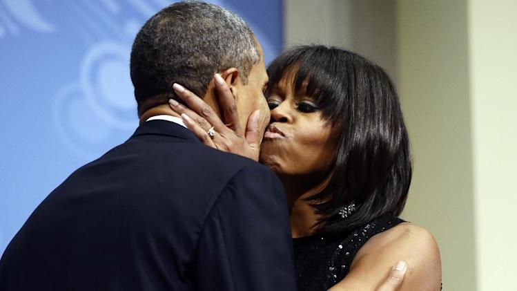 President Barack Obama kisses first lady Michelle Obama as they speak to supporters and donors at an inaugural reception for the 57th Presidential Inauguration at The National Building Museum in Washington, Sunday, Jan. 20, 2013. (AP Photo/Charles Dharapak)