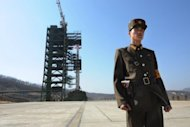 "A North Korean soldier stands guard in front of the Unha-3 rocket at Tangachai -ri space center on April 8, 2012. North Korea has vowed to launch satellites ""one after another"", vigorously rejecting international condemnation of an April 13 launch that was seen overseas as a disguised ballistic missile test"