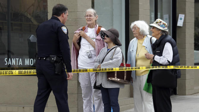 Police Lt. Robert Almada tells bystanders that a mountain lion, found in the courtyard of an office building on Second Street in the downtown urban core of Santa Monica, Calif., unfortunately had to be killed Tuesday, May 22, 2012.  Discovered shortly before 6 a.m. by a maintenance worker, animal officers and police tried several less-than-lethal methods to subdue the cat, but it continued to try to move out of the area and was shot and killed by police. (AP Photo/Reed Saxon)