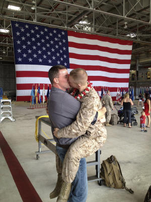 """Sgt. Brandon Morgan, right, is embraced by his partner Dalan Wells in a helicopter hangar at a Marine base in  Kaneohe Bay, Hawaii, upon returning from a six-month deployment to Afghanistan in this photo made Wednesday, Feb. 22, 2012.  The photo, made some five months after the repeal of the military's """"don't ask don't tell"""" policy prohibiting gay servicemen from openly acknowledging their sexuality, is among the first showing a gay active duty serviceman in uniform kissing his partner at a homecoming. (AP Photo/David Lewis)"""