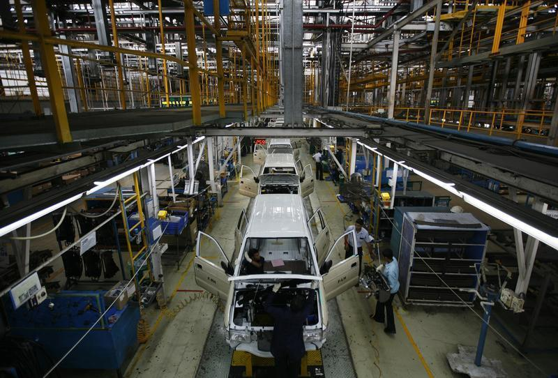 Employees work on the Chevrolet Tavera assembly line inside a plant of General Motors India Ltd. at Halol