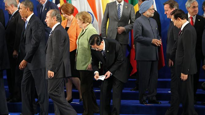 China's President Hu Jintao, center, is left behind by other leaders of the G-20 while they walk off the stage as the flag that marked his spot got stick to his shoe after posing for the family photo of the G-20 Summit in Los Cabos, Mexico, Monday, June 18, 2012. From left are Italy's Prime Minister Mario Monti, President Barack Obama, Mexico's President Felipe Calderon, Australia's Prime Minister Julia Gillard, Germany's Chancellor Angela Merkel, President Hu, India's Prime Minister Manmohan Singh, British Prime Minister David Cameron, South Korea's President Lee Myung-bak and Chile's President Sebastian Pinera. (AP Photo/Andres Leighton)
