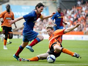 A Dundee United defender attempts to tackle Barcelona's Lionel Messi during a friendly match at Tannadice Stadium in Dundee, Scotland, on July 26, 2008