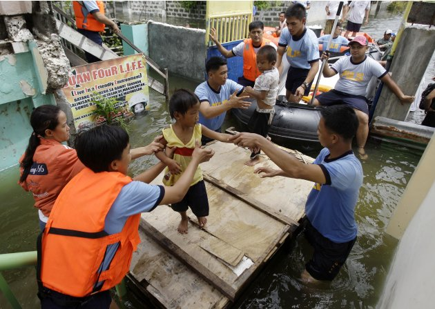 Rescuers move children to an evacuation center at Malabon city, north of Manila, Philippines on Wednesday, Aug. 1, 2012. Fierce winds and heavy rains from the slow-moving Typhoon Saola battered the co