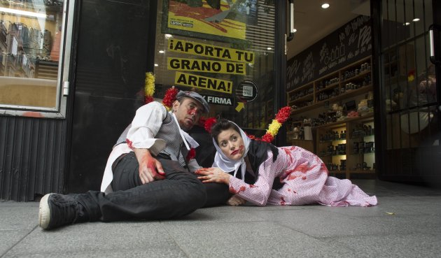 Animal rights activists dressed in traditional costume and covered in fake blood lie on the ground during a protest against bullfighting in Madrid